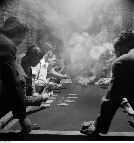 Une partie de barbotte, le rapide jeu de dés qui faisait la renommée de Montréal. Il s'agit ici d'une mise en scène pour un photoreportage, les joueurs étant en fait des agents de l'escouade de la moralité. Photo de Michael Rougier pour le Standard, 1947.