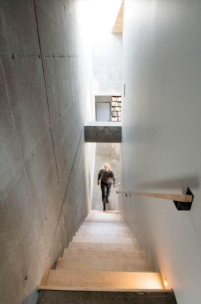 On accède à l'étage par un escalier qui longe le mur de béton et qui laisse apparaître une poutre porteuse.