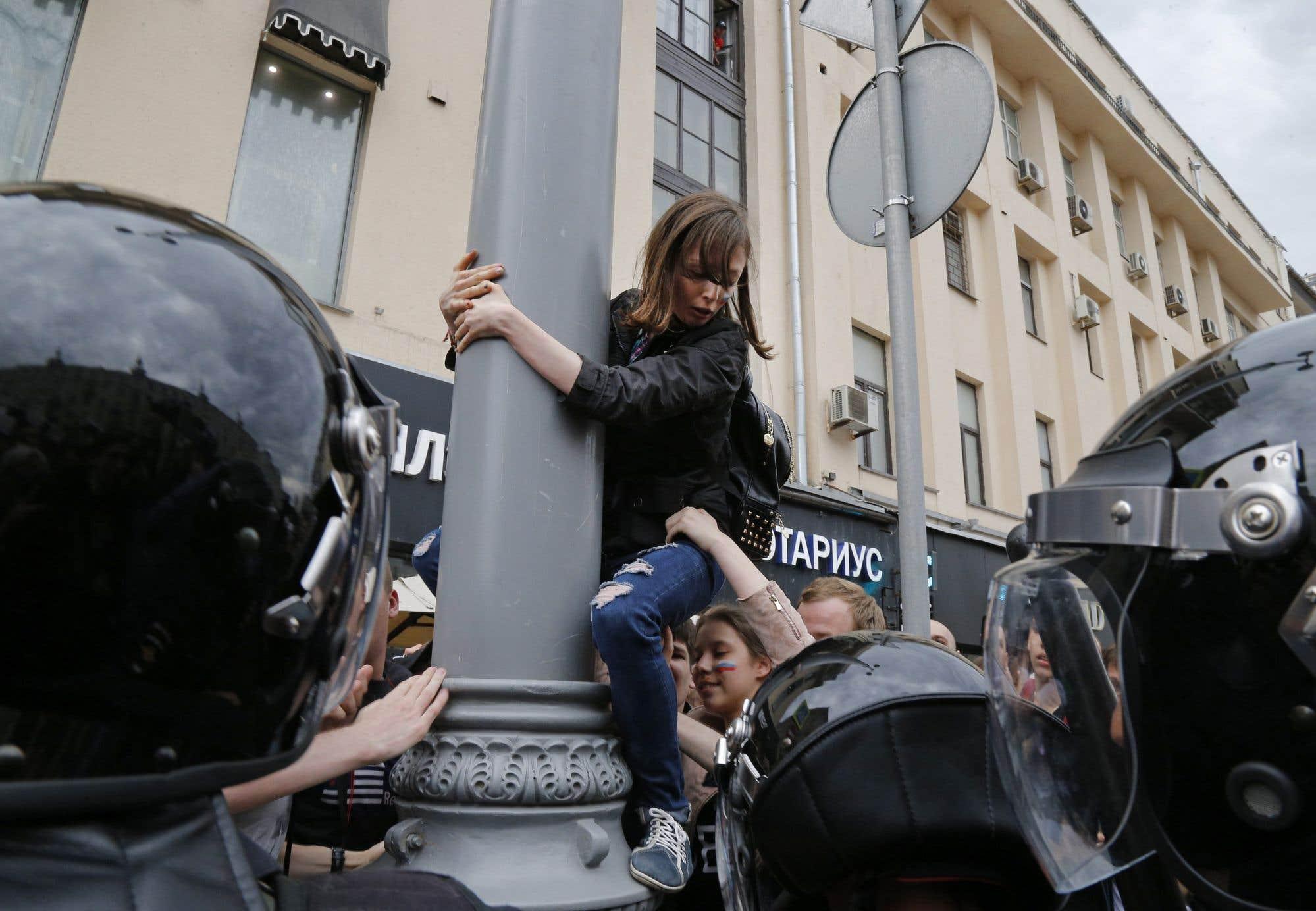 Une manifestante se fait tirer en bas d'un lampadaire à Moscou ce lundi. L'opposant au président russe Alexei Navalny avait tenté de reproduire les manifestations qui avaient secoué la Russie il y a trois mois. Il s'est fait arrêter par la police à l'extérieur de sa maison alors qu'il se dirigeait vers la manifestation de Moscou. M. Navalny souhaite se présenter comme prétendant au poste de Vladimir Poutine aux prochaines élections.