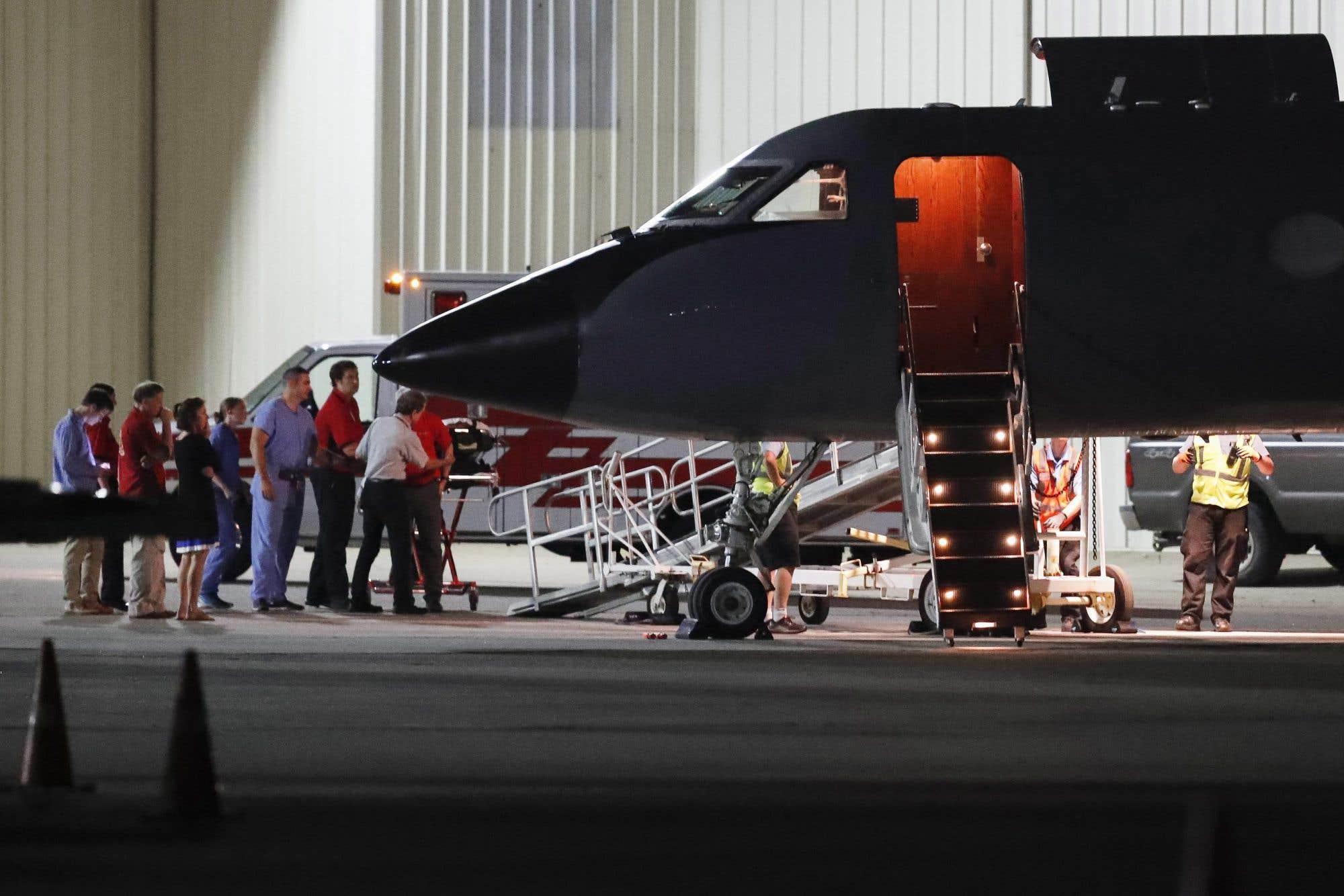 Du personnel médical et des visiteurs se rassemblent à l'avant de l'avion transportant Otto Warmbier, un étudiant de 22 ans de l'Université de Virginie. M. Warmbier avait été emprisonné en Corée du Nord en mars 2016 et serait dans le coma depuis plusieurs mois. Il a été retourné aux États-Unis mardi.