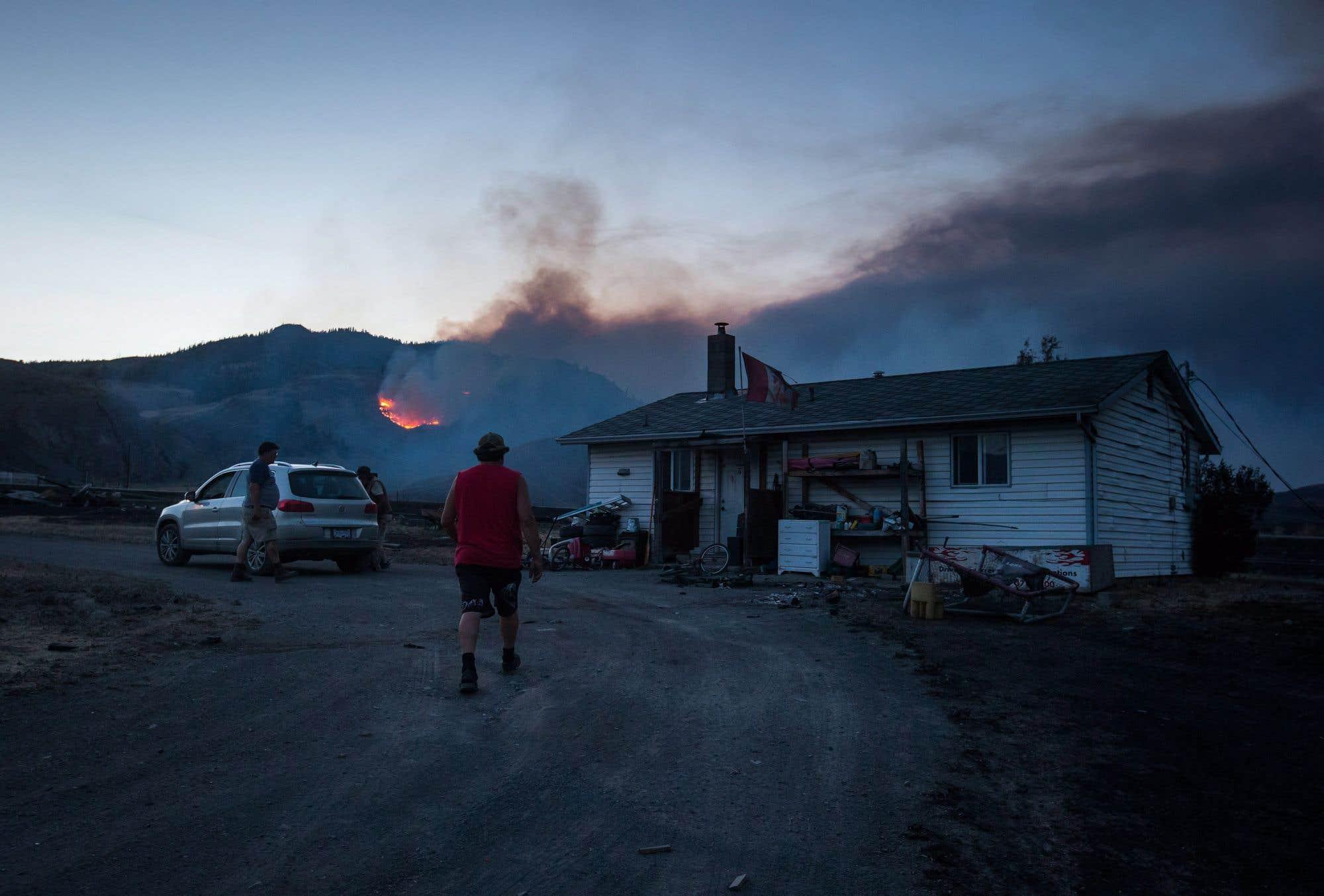 Darin Minnabarriet, de la communauté autochtone Ashcroft, marche vers sa maison qui a survécu à un feu de forêt pour vider son congélateur. Des feux de forêt ont occupé les autorités de la Colombie-Britannique toute la semaine. Des pompiers québécois seront envoyés en renfort lundi pour aider à combattre les incendies, qui ont forcé jusqu'ici l'évacuation de 16 250 personnes. Consultez notre texte sur le sujet