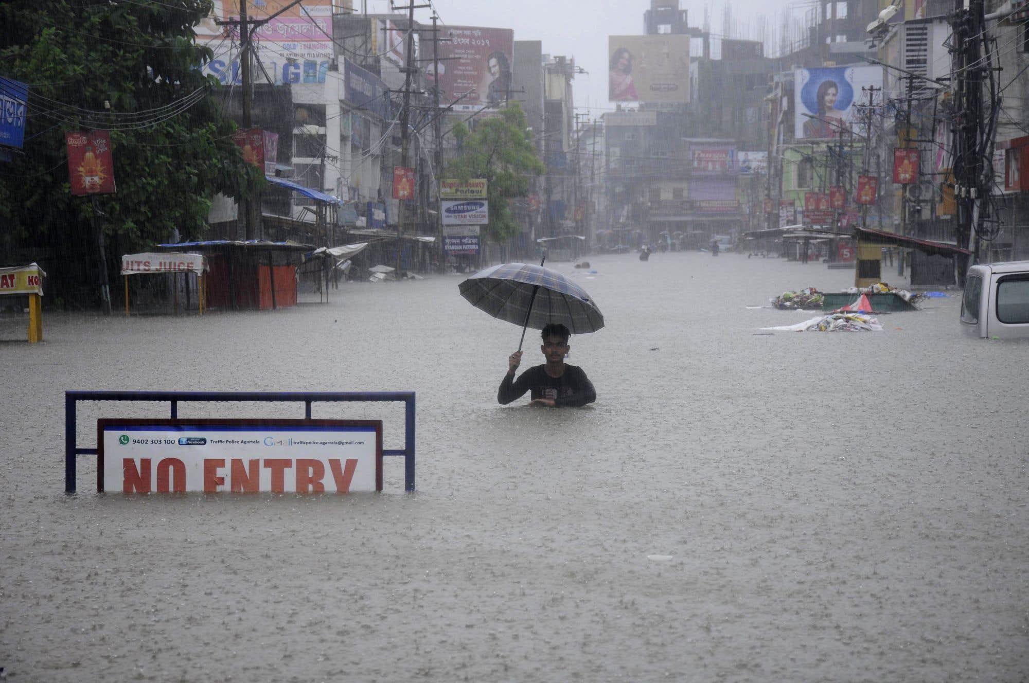 Inondations à Agartala, capitale de la province au nord-est de l'Inde de Tripura. Un homme marche le long d'une rue alors qu'une forte pluie s'abat sur la région.