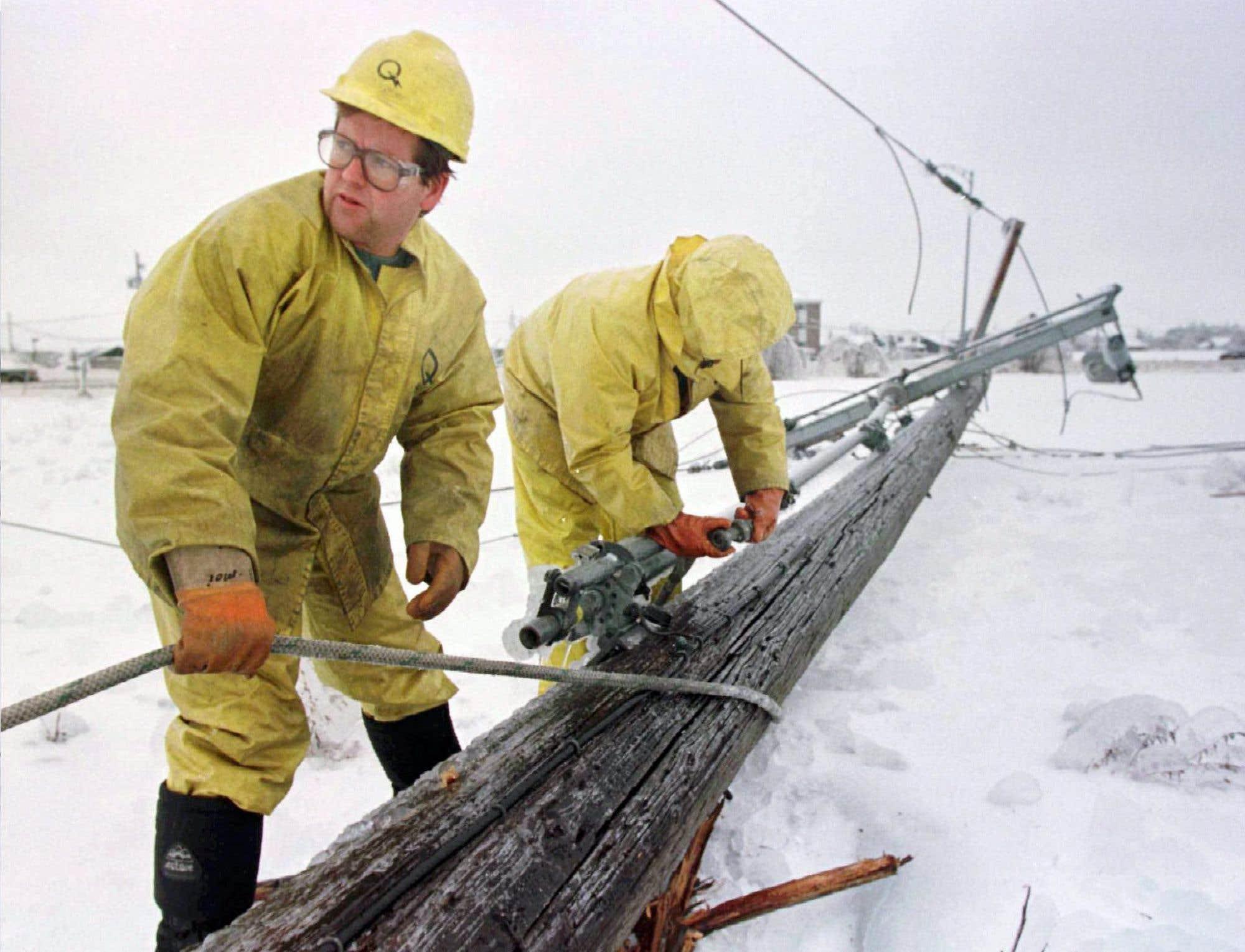 Des employés d'Hydro-Québec réparent un poteau électrique projeté au sol en raison du verglas. Au terme de la tempête, 16000poteaux comme celui-ci se sont effondrés.