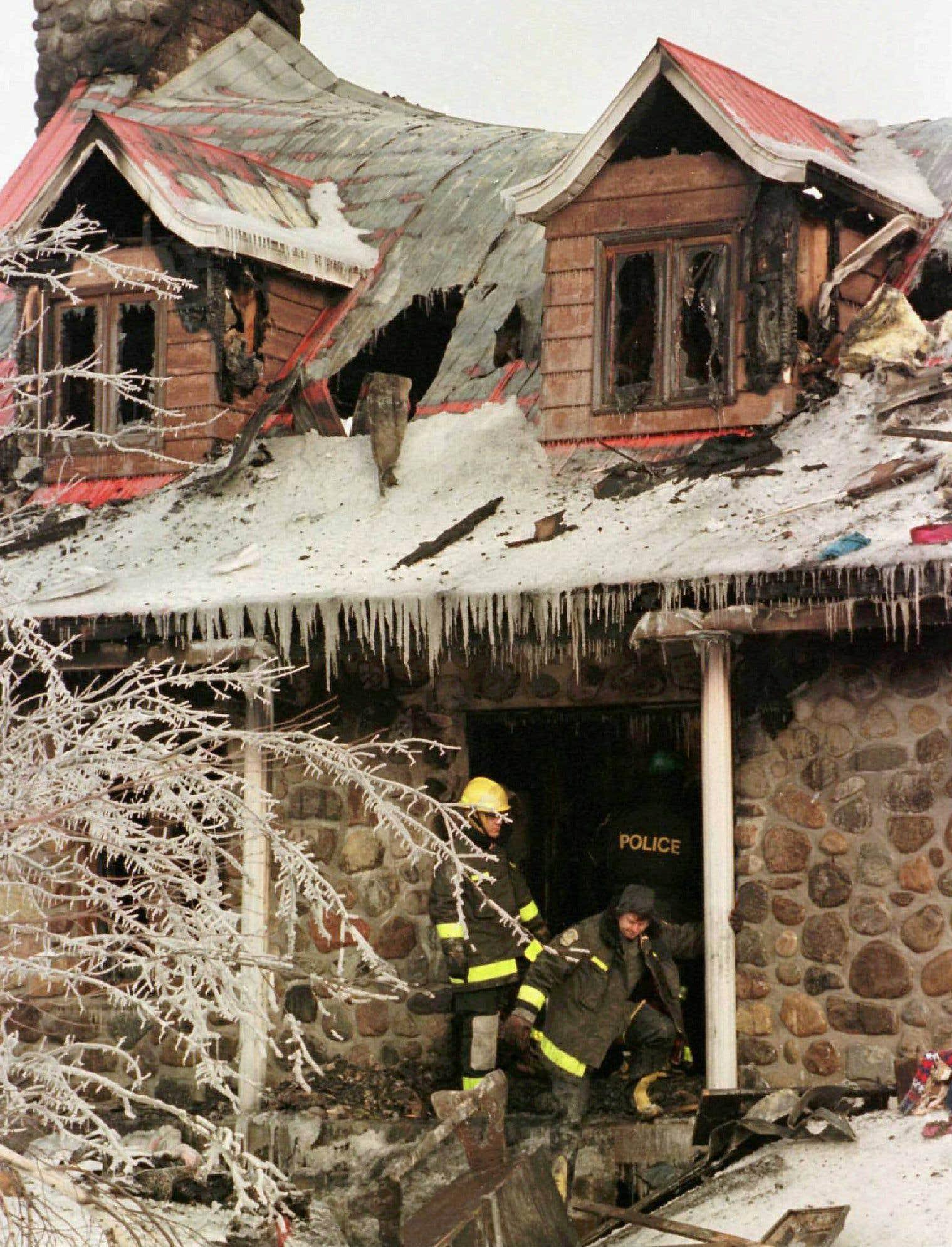 Des pompiers quittent une maison incendiée à Carignan, en banlieue de Montréal. Quatre membres d'une même famille ont été gravement brûlés à la suite du brasier provoqué par une génératrice au gaz naturel.
