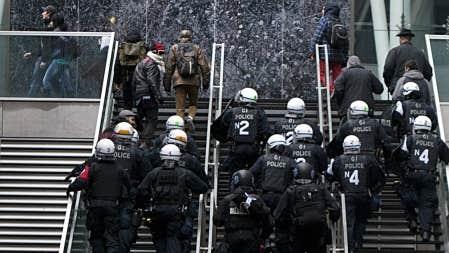 Des manifestants ont gravi un balcon de la Caisse de dépôt, poursuivis par les policiers.