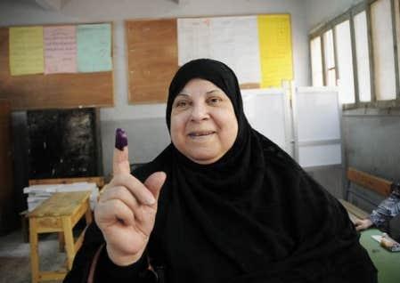 Une femme égyptienne montre son doigt taché d'encre après avoir voté dans un bureau à Gizeh, en Égypte.