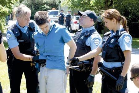 Des policiers passant les menottes à un homme arrêté aux abords du circuit Gilles-Villeneuve dimanche, jour du Grand Prix du Canada.