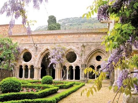 Au printemps, les jardins du cloître de l'abbaye de Fontfroide, à Narbonne, prennent les couleurs blanche et mauve de la glycine centenaire, puis le rouge des géraniums.