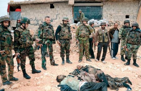 Des vidéos montrant des soldats syriens tranchant les oreilles d'insurgés tombés au combat ont été remises à l'Observatoire syrien des droits de l'homme. Sur cette photo, l'armée syrienne encercle les corps de deux rebelles dans la ville d'Alep.