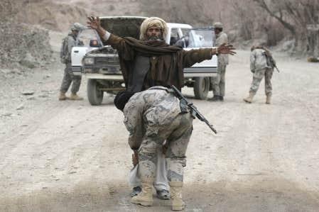 Un policier afghan fouillait hier un compatriote à un poste de contrôle près de la base militaire Tillman.