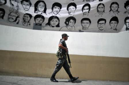 Un soldat marche sous une banderole montrant des victimes de la guerre civile qui a ensanglanté le Guatemala, au cours d'une manifestation réclamant l'ouverture des archives militaires, en février dernier.