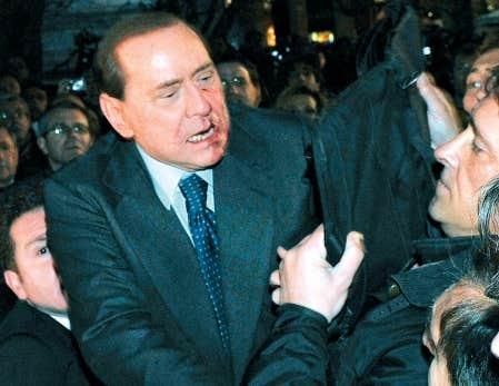 Le visage ensanglanté, Silvio Berlusconi reçoit l'aide de policiers après avoir été victime d'une agression à l'issue d'un rassemblement politique, hier, à Milan.