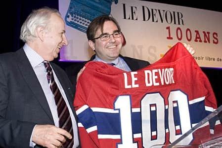 Bernard Descôteaux reçoit du copropriétaire du Canadien de Montréal, Andrew Molson, un chandail du Tricolore arborant le numéro 100 pour les 100 ans du quotidien indépendant.