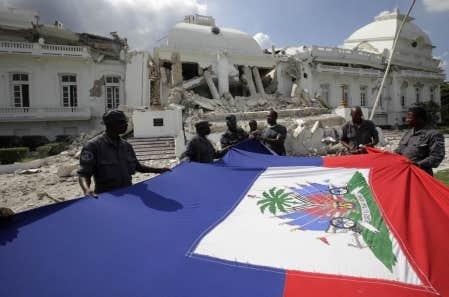 Des officiers de police tendent le drapeau national haïtien qu'ils ont récupéré dans les ruines du palais national, hier, à Port-au-Prince. La reconstruction est déjà au programme des pays donateurs.