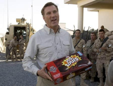 Le ministre Maxime Bernier distribuant des gâteaux en Afghanistan en octobre 2007, à la suite d'une opération improvisée.