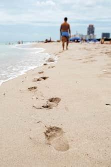 Un touriste marche sur une plage de Miami, en Floride. <br />