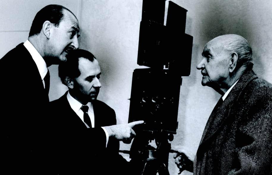 Le fondateur du Ouimetoscope, Léo-Ernest Ouimet (à droite), discute autour d'une caméra Pathé avec le producteur Michel Costom et Guy-L. Coté (au centre), fondateur de la Cinémathèque québécoise.
