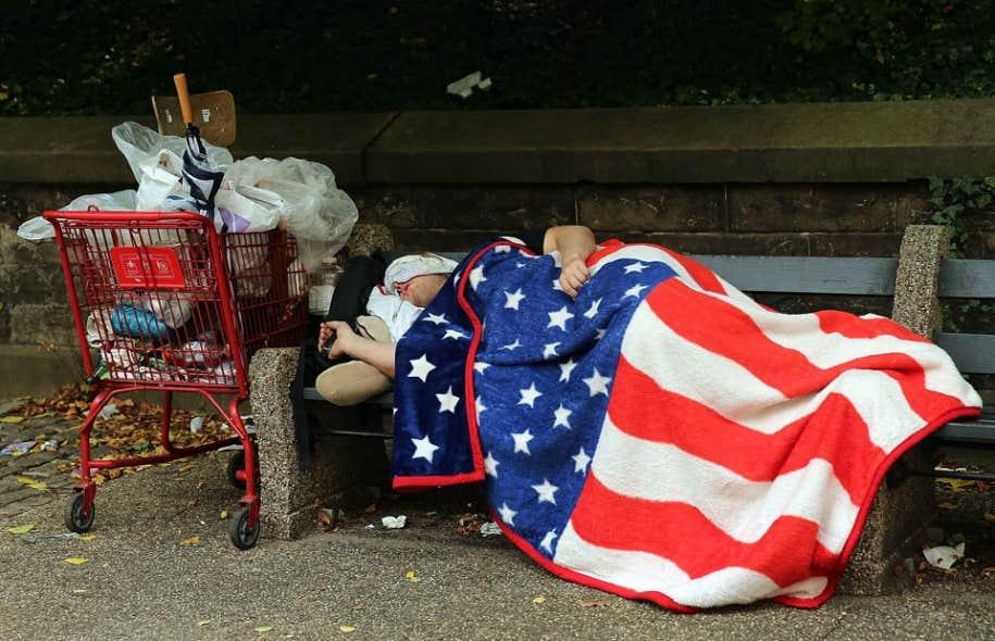 Un sans-abri sur un banc de parc à New York, ville où la richesse côtoie l'extrême pauvreté.