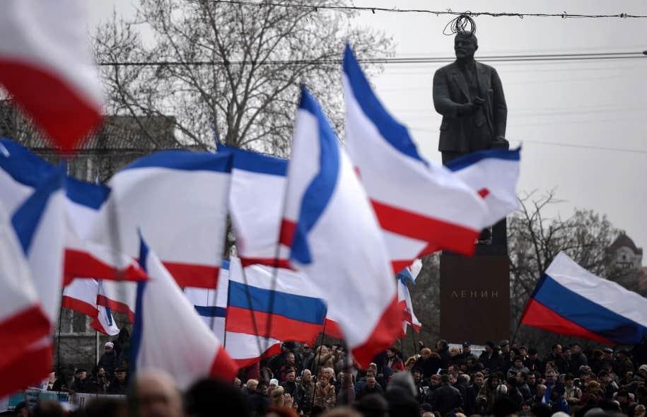 Des manifestants ont brandi des drapeaux russes et criméens à Simferopol, dimanche, pour démontrer leur appui au rattachement à la Russie.