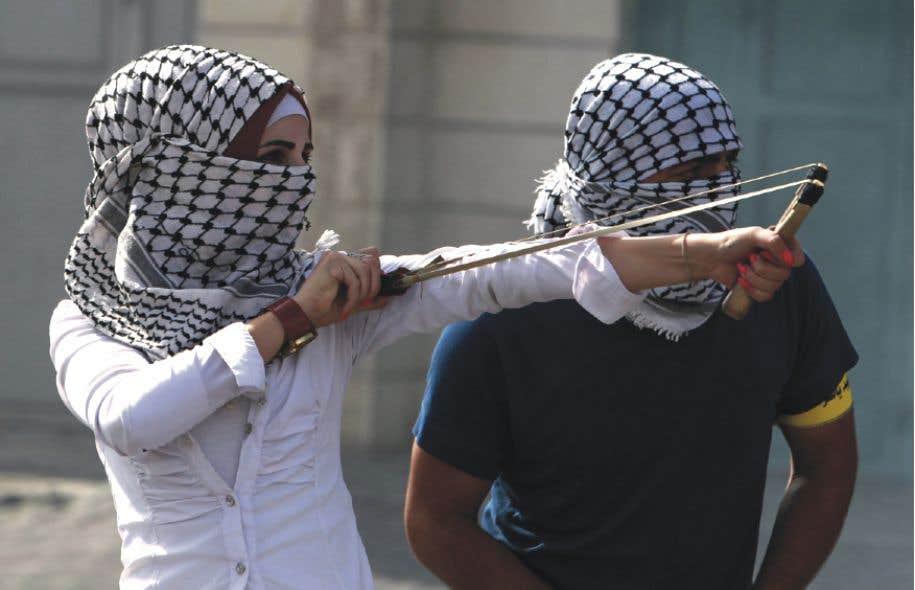 Une jeune femme attaque au lance-pierres des soldats israéliens. Les Palestiniennes sont plus nombreuses à participer aux affrontements quotidiens avec le Tsahal.