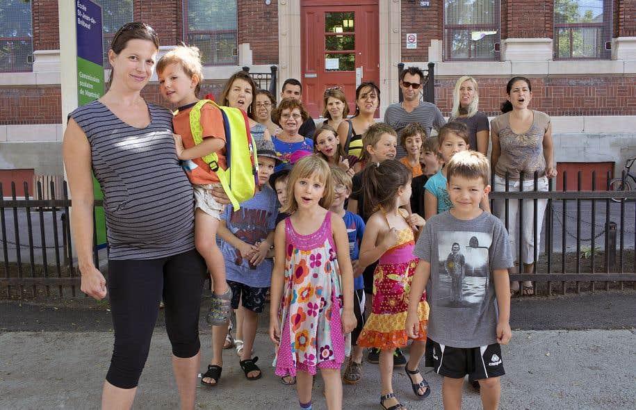 Des parents et des enfants du regroupement Je protège mon école publique devant l'école Saint-Jean-de-Brébeuf, à Montréal, en août2015. Partout au Québec, des dizaines de milliers de parents ont érigé des barrières humaines pour dénoncer les compressions en éducation.