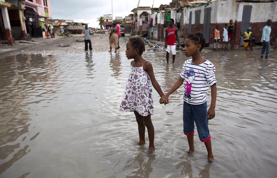 Deux fillettes se tenant par la main dans les rues inondées des Cayes après le passage de l'ouragan «Matthew», en octobre dernier
