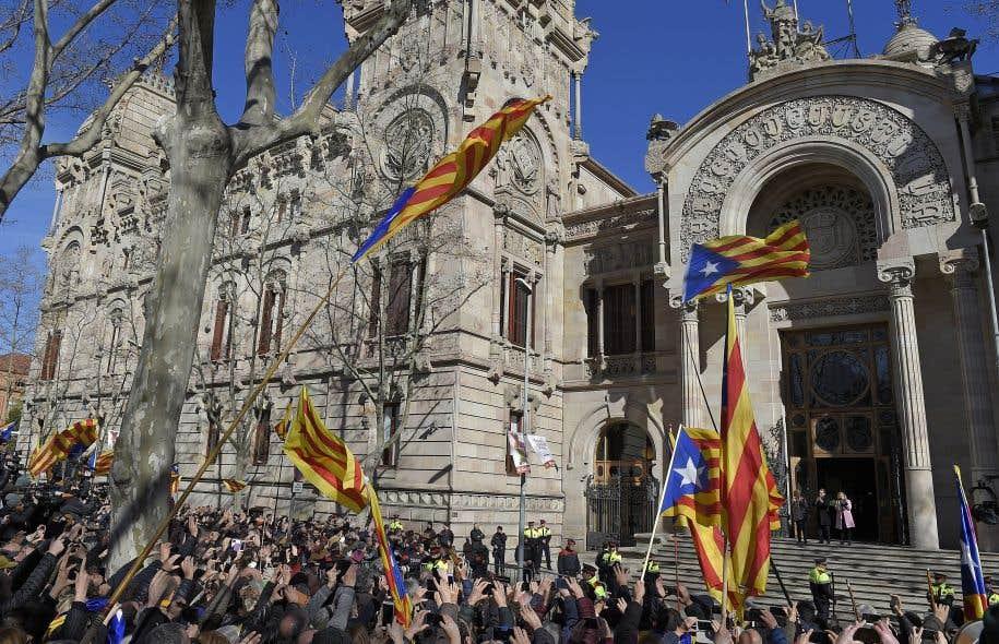 Artur Mas et ses deux coaccusées, Joana Ortega et Irene Rigau, ont salué la foule venue les soutenir à la sortie de la Cour supérieure de Catalogne, lundi.