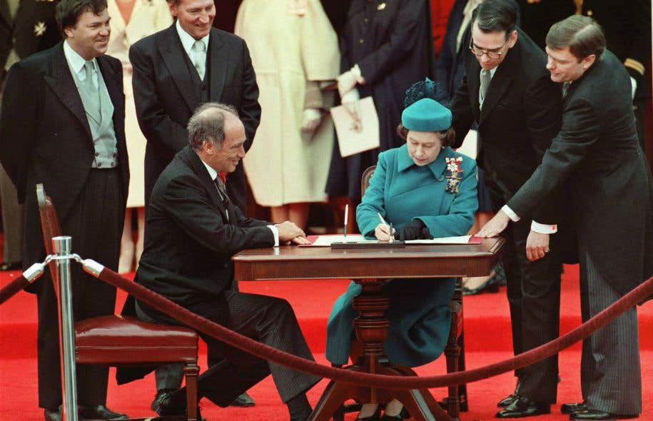 La reine Élisabeth II et le premier ministre Pierre Elliott Trudeau lors de la signature de la Constitution du Canada en avril 1982.