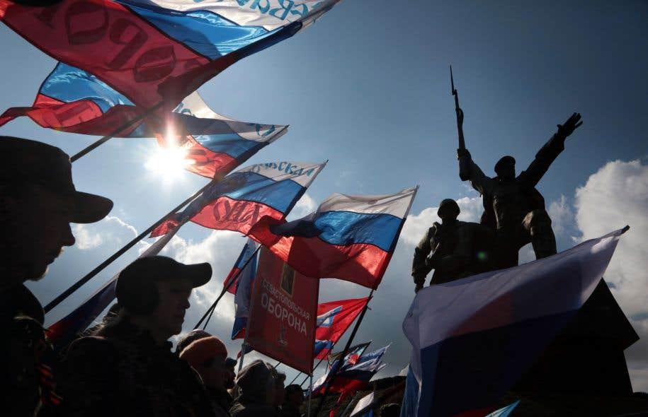 Des Russes brandissent le drapeau national pour fêter le troisième anniversaire de l'annexion de la Crimée à Sébastopol, le 18 mars 2017.