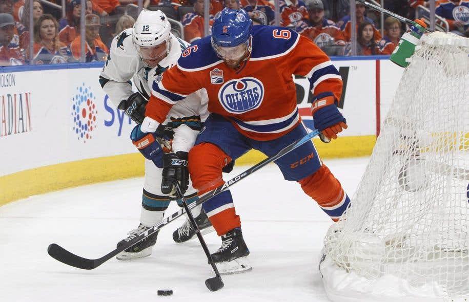 Le défenseur des Oilers Adam et l'attaquant des Sharks Patrick Marleau luttent pour la possession de la rondelle.