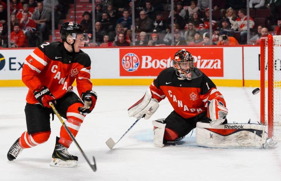 Le gardien Eric Comrie d'Équipe Canada et son coéquipier Joe Hicketts, lors d'un match préliminaire pendant les Championnats du monde de hockey junior de l'IIHF en 2015