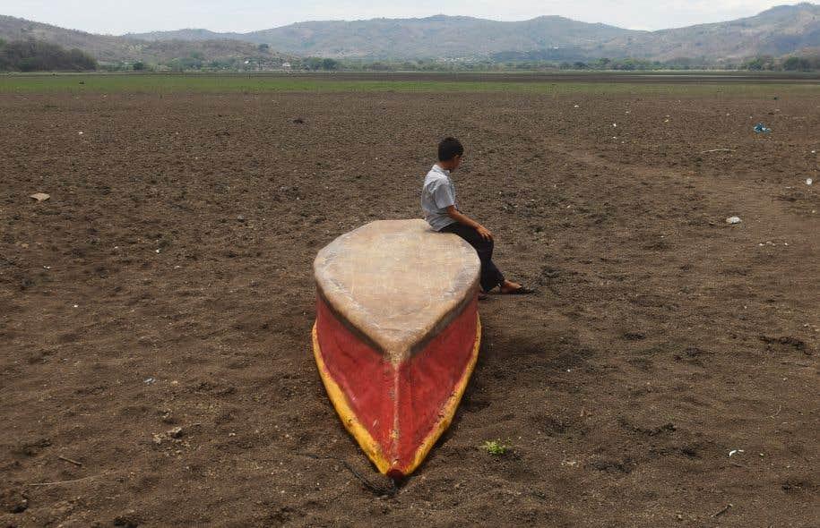 Un garçon est assis sur un bateau abandonné sur ce qu'il reste du lac Atescatempa, qui a séché en raison de la sécheresse et des températures élevées.