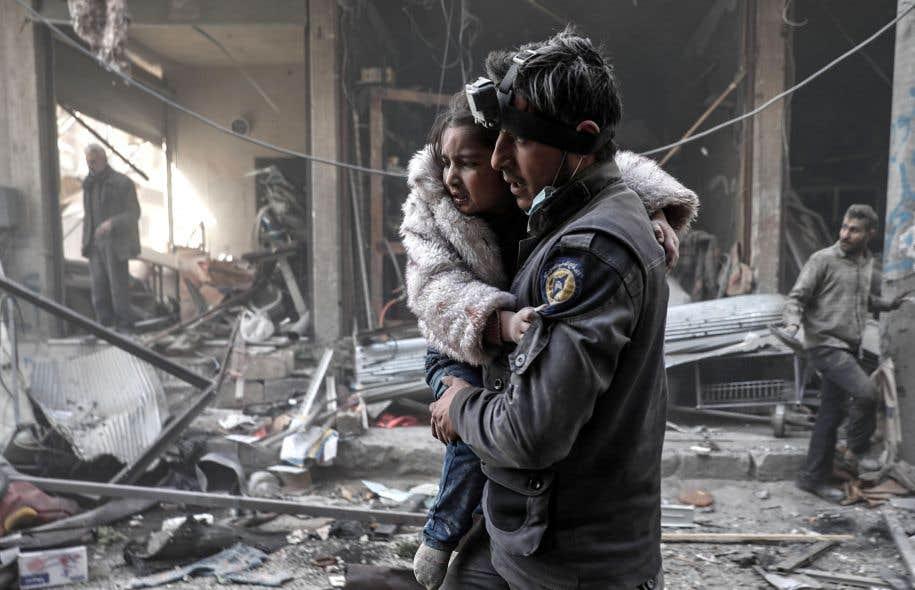 Un homme porte une fillette blessée dans les décombres de Damas, en Syrie. Pourquoi le cadre juridique international n'est-il pas respecté, et les civils épargnés?