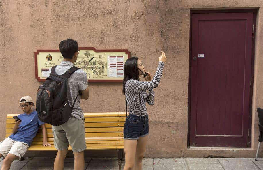 Des touristes sud-coréens font la file pour se prendre en photo devant la porte de secours du théâtre Petit Champlain.