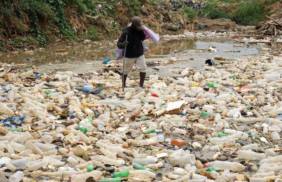 Un Ivoirien cherche des objets de valeur dans un amas de déchets, surtout de plastique, près d'Abidjan.