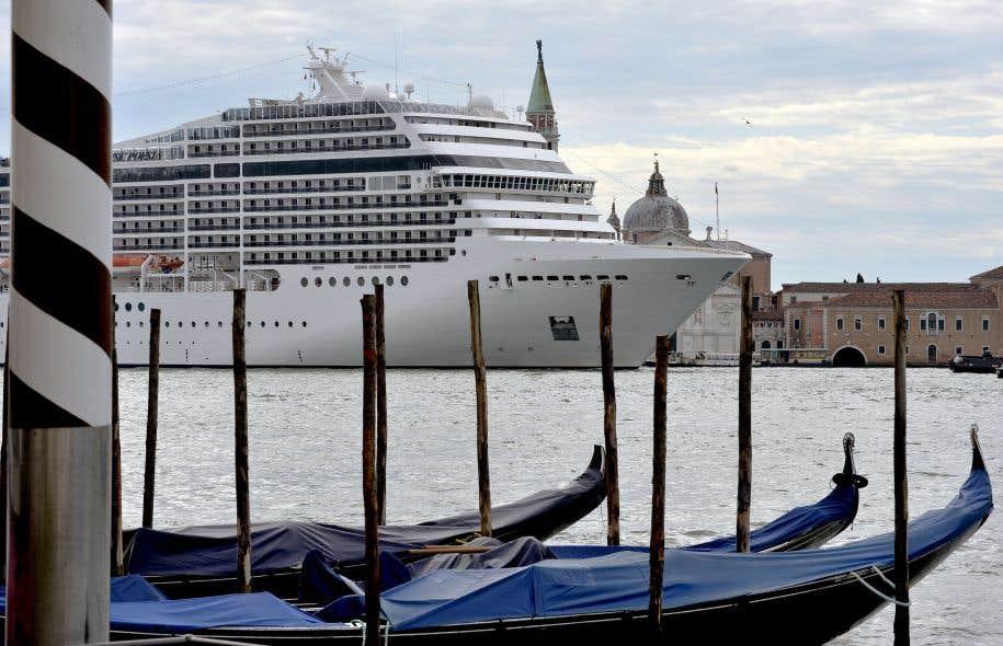 Un bateau de croisière passe tout près de gondoles devant la place Saint-Marc, à Venise.