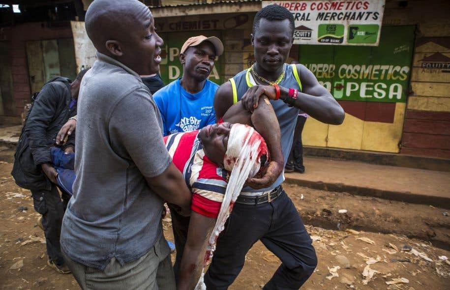 Un homme blessé par des policiers est aidé dans les bidonvilles de Kawangware à Nairobi le 11 août 2017.
