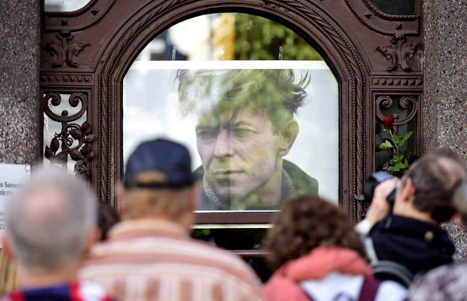 Des gens assistent au dévoilement d'une plaque commémorative dédiée au musicien David Bowie, à l'appartement qu'il a jadis occupé à Berlin.