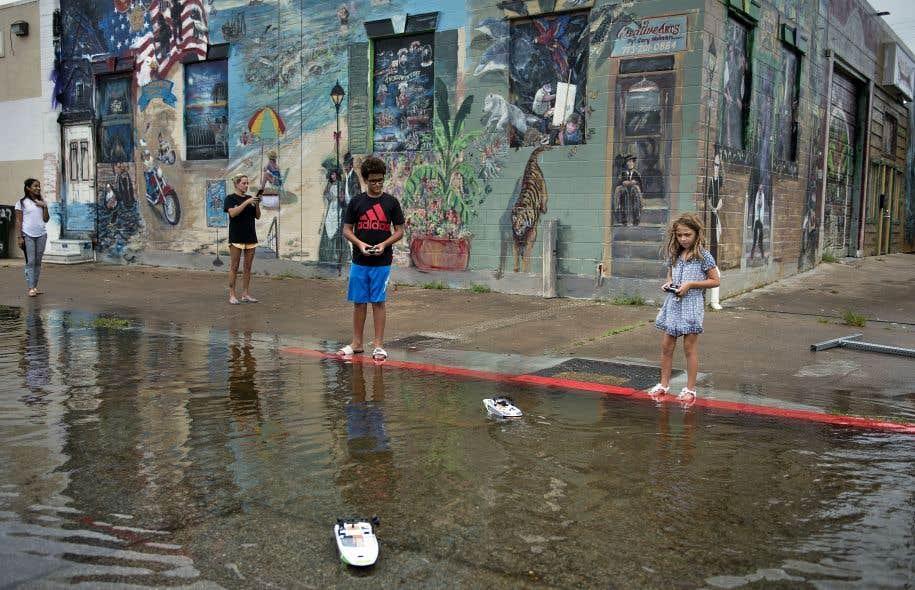 """Certains font de l'anxiété, d'autres en profitent pour s'amuser. Les catastrophes climatiques sont des territoires d""""extrêmes. Ici, des enfants de Galveston, au Texas, après le passage de l'ouragan Harvey."""