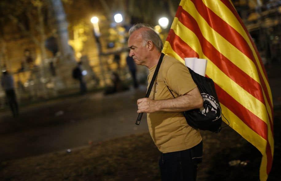 Un homme marche avec son drapeau aux couleurs de l'indépendance catalane dans les rues de Barcelone, mardi.