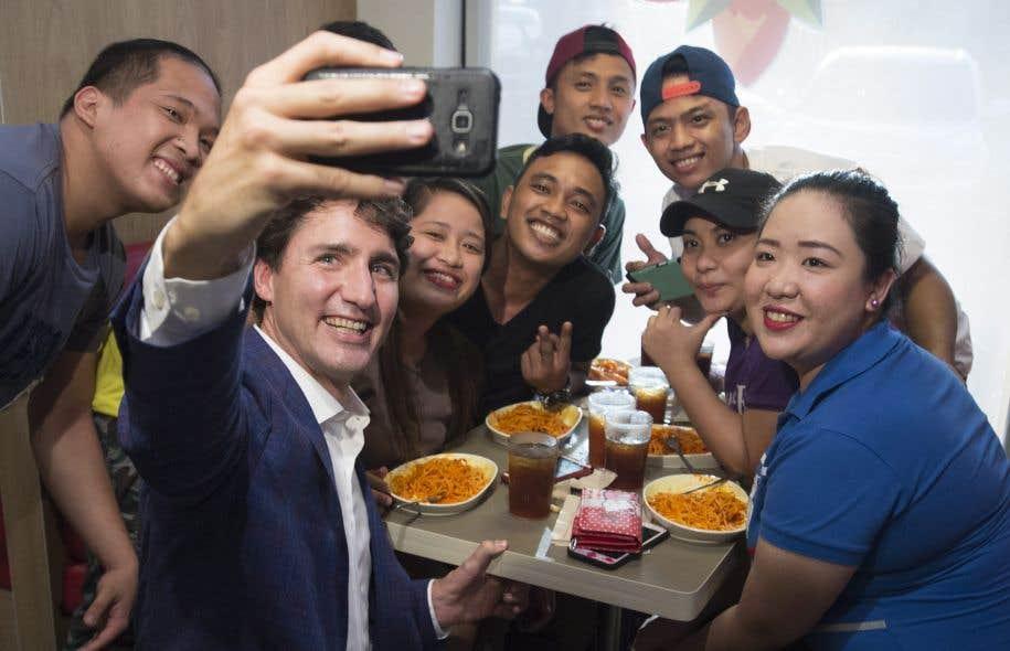 Le premier ministre Justin Trudeau prend une photo avec des clients d'un restaurant à Manille, aux Philippines.