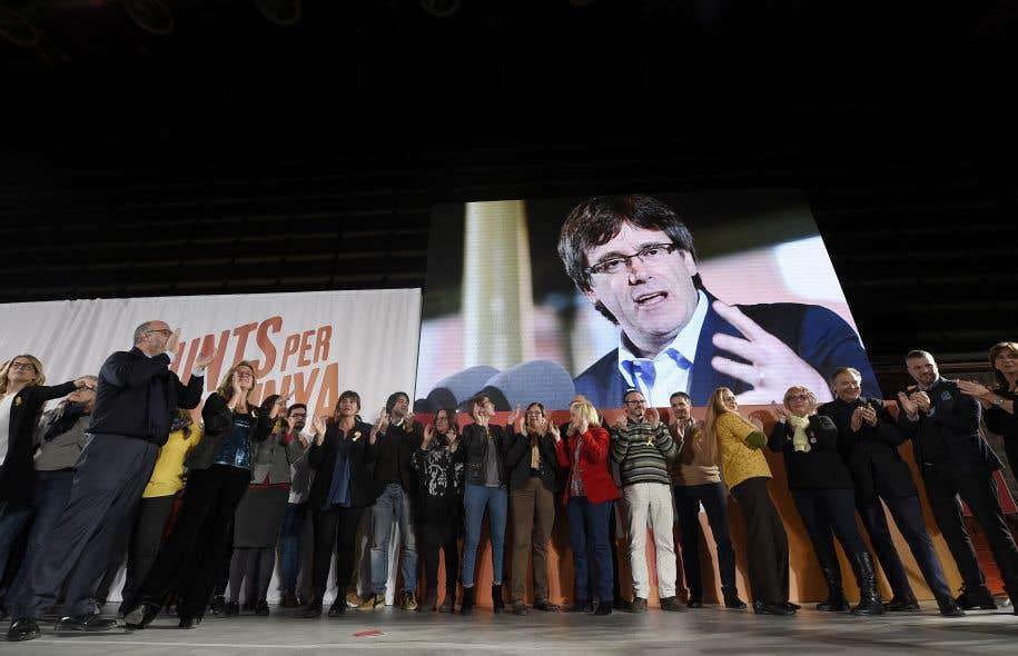 Des sympathisants indépendantistes applaudissent sous la photo du président catalan démis de ses fonctions, Carles Puigdemont, qui présentera sa candidature aux nouvelles élections régionales le 21 décembre.
