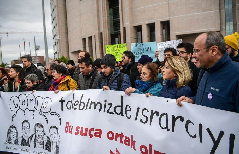 Des manifestants brandissaient mardi une banderole pour soutenir un groupe d'universitaires accusés d'infractions terroristes pour avoir signé une pétition il y a presque deux ans.