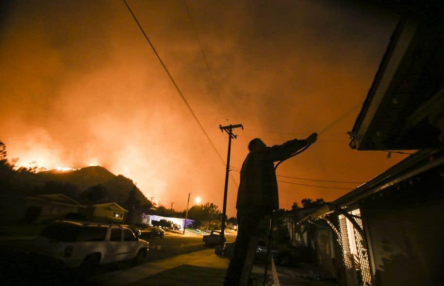 Un homme asperge sa maison d'eau alors qu'un immense incendie se rapproche de Santa Paula, au nord-ouest de Los Angeles.