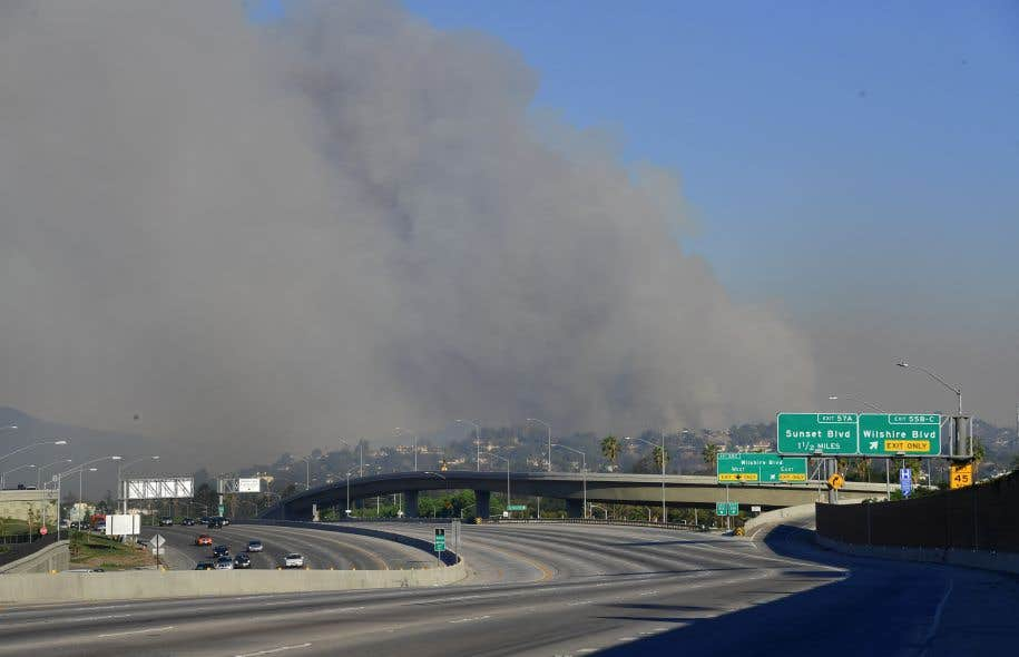 Un nuage de fumée noire enveloppe le quartier Bel-Air de Los Angeles, situé à l'est de l'autoroute 405 désormais fermée à la circulation.