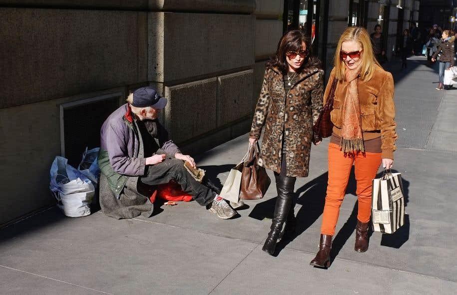 Deux femmes passent devant un mendiant sur Madison Avenue à New York. Aux États-Unis, les seuls à s'être remis complètement de la terrible crise et à avoir même amélioré leur sort sont les ménages de revenus supérieurs.