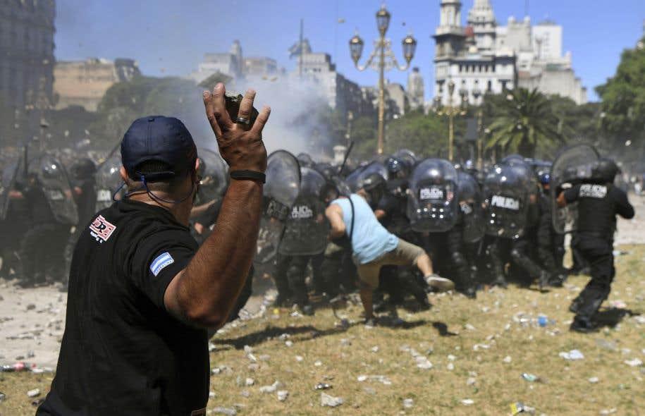 Un manifestant lance une pierre à des agents de la police antiémeute lors d'une manifestation contre les réformes des retraites, à Buenos Aires, mardi.