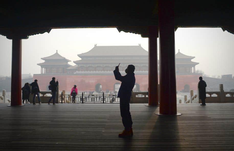 Un homme portant un masque prend une photo alors qu'il visite la Cité Interdite à Pékin, le 21 décembre 2016.