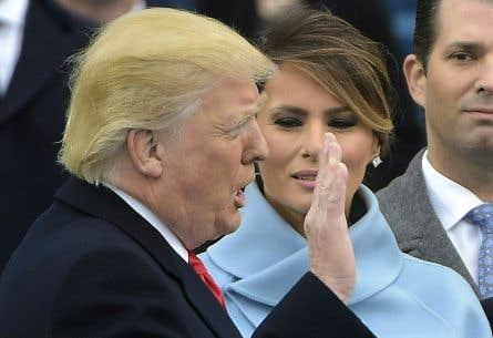 Donald Trump au moment de prêter serment sur les bibles — celle que lui a donnée sa mère lorsqu'il était enfant, et celle ayant appartenu à Abraham Lincoln — que tient la première dame, Melania.