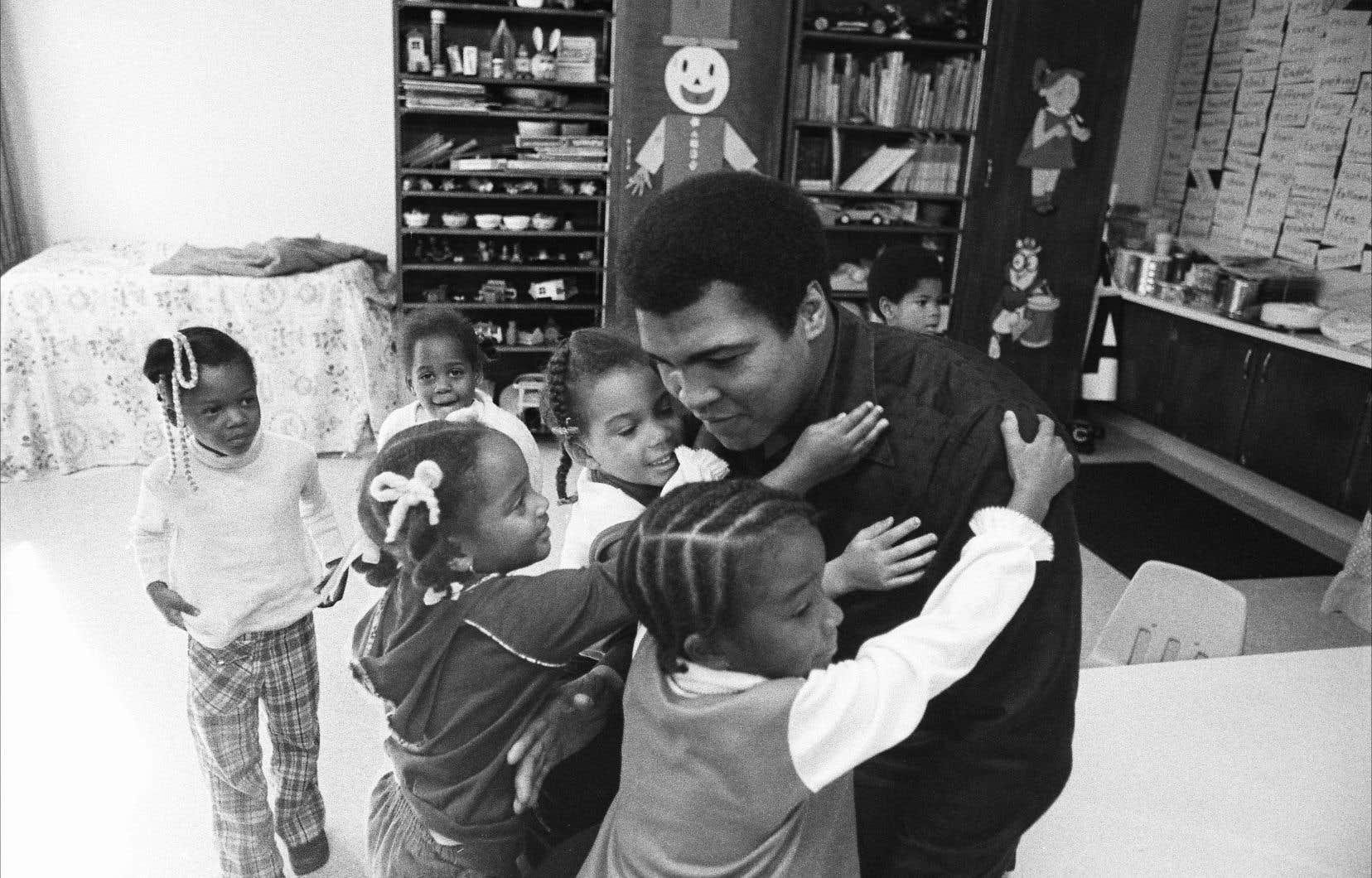 Mohamed Ali entouré de petits élèves lors d'une visite à son ancienne école à Louisville, au Kentucky, en 1977.